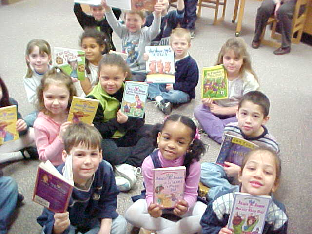 Photo of kids holding up books